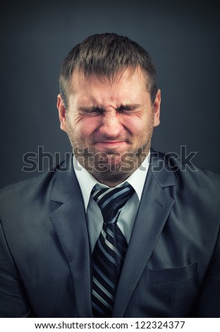 Stressed businessman with screwed-up eyes - stock photo