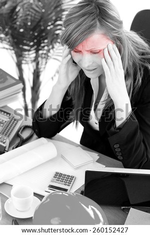 Stressed businesswoman having a headache in the office - stock photo
