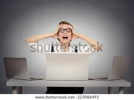 Stressed businesswoman sitting at table in front of multiple computers in her office having nervous breakdown. Negative human face expressions, emotion feeling body language - stock photo