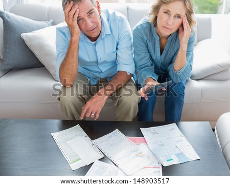 Stressed couple sitting on their couch paying their bills smiling at camera at home in the living room - stock photo