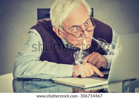 Stressed elderly man using computer blowing steam from nose frustrated sitting at table isolated on gray wall background. Senior people and technology concept  - stock photo