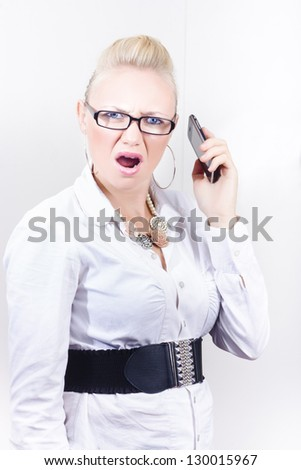 Stressed employee expressing mobile phone rage when communicating with frustrating clients in workplace - stock photo