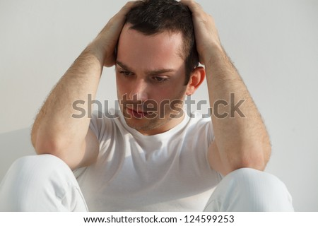 Stressed handsome young man sitting on floor, wearing white t-shirt and pants. Studio shot, natural light. - stock photo