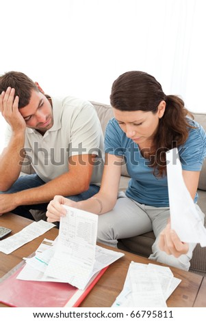 Stressed man and woman looking at their bills in the living room at home - stock photo