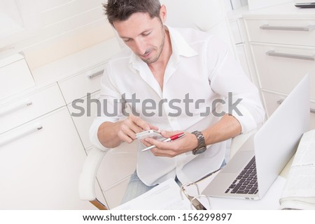 Stressed man in the office making new date with her telephone. - stock photo