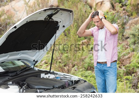 Stressed man looking at engine of his car - stock photo
