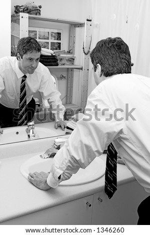stressed man looking in mirror - stock photo