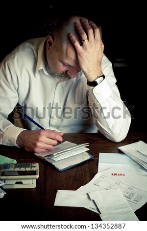 Stressed man with checkbook struggling while working on household finances - stock photo