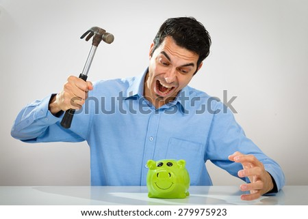 Stressed man with hammer breaking the green piggy bank - stock photo