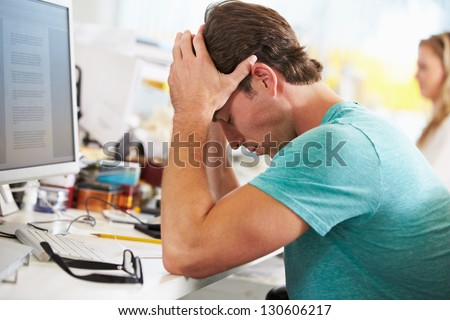 Stressed Man Working At Desk In Busy Creative Office - stock photo