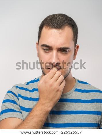 stressed mid adult businessman biting fingernails  - stock photo