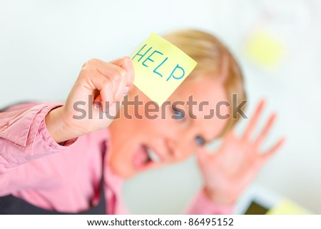 Stressed modern business woman showing sticky note with help word - stock photo