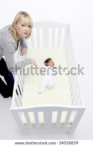 Stressed Mother Looking At Baby In Cot - stock photo