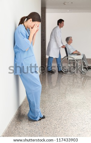 Stressed nurse leaning against wall with doctor pushing patient in wheelchair - stock photo