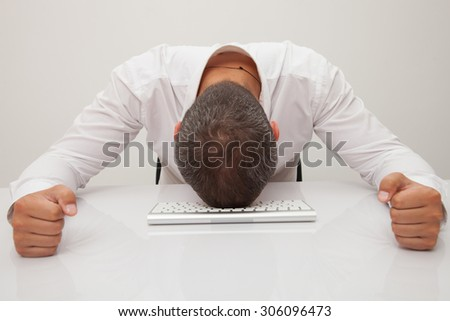 Stressed out businessman. Man frustrated with his computer. Isolated on white background  - stock photo