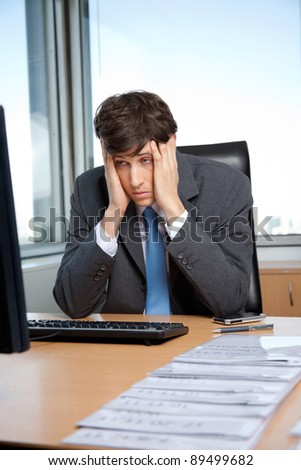 Stressed out businessman sitting at his desk in front of computer - stock photo