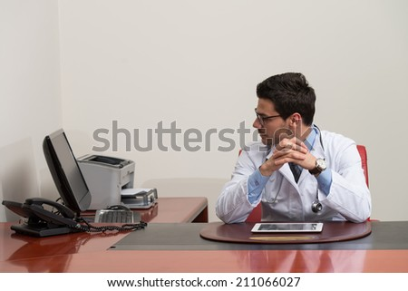 Stressed Out Doctor With Hands Clasped Sitting At Table In Conference Room - stock photo