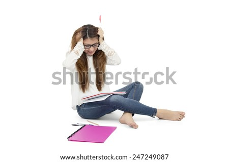 Stressed out woman student trying to study against a white background - stock photo