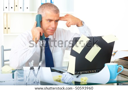 Stressed overworked mature businessman sitting at desk with phone and looking at laptop with many notes stickers - stock photo