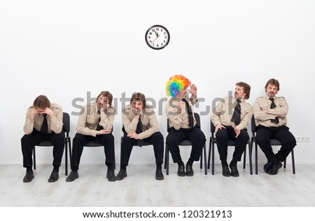 Stressed people waiting for a job interview - with a clown keeping up the good spirit - stock photo