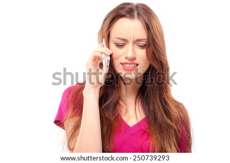 Stressed, tired and worried young woman talking on the phone isolated on white background - stock photo