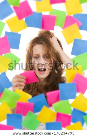 Stressed womam with pink note surrounded by colorful papers - stock photo