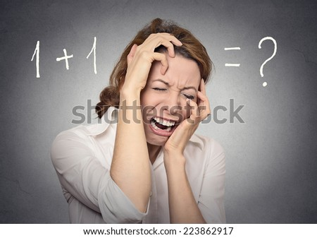 stressed woman can't solve math financial problem isolated on grey wall background. Human face expressions, emotions, feelings - stock photo