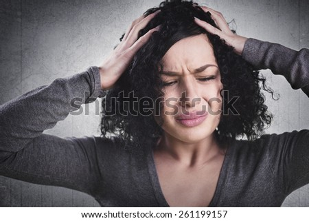 Stressed woman having headache and being despaired, isolated on grey background. - stock photo
