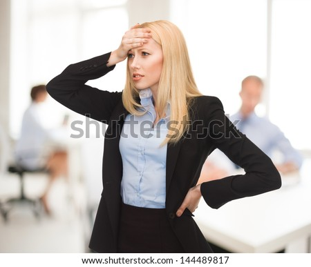 stressed woman holding her head with hand in office - stock photo