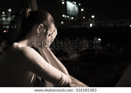 Stressed woman in a nigh time setting.  - stock photo