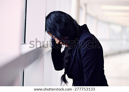 Stressed woman putting her forehead on the office wall - stock photo