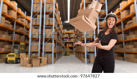 Stressed woman with helmet trying to catch flying parcels in a warehouse - stock photo