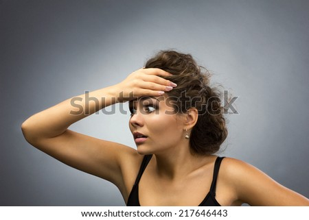 stressed young brunette woman holding her head, isolated on grey light background  - stock photo