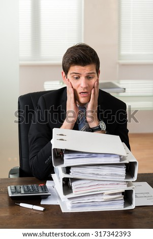 Stressed Young Businessman Looking At Stack Of Folders In Office - stock photo