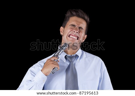 Stressed young businessman with a gun pointing to his head (isolated on black) - stock photo