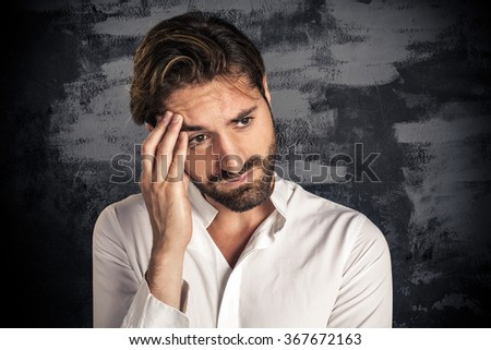 Stressed young businessman with hand on the head - stock photo