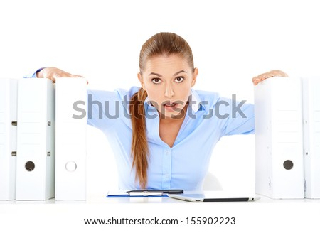 Stressed young businesswoman staring at the camera from between two large office files over a white background - stock photo