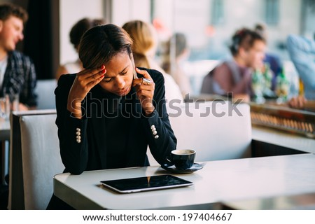 Stressed young businesswoman talking on the phone in coffee shop - stock photo