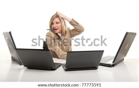 Stressed young woman using four laptops - stock photo