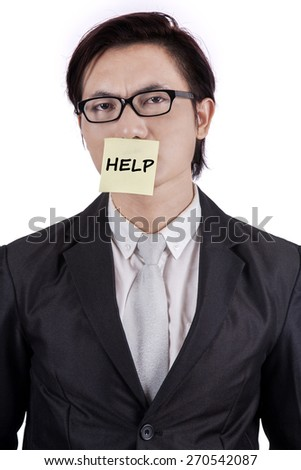 Stressful businessman wearing formal suit and attach a paper note with a help text on his mouth - stock photo
