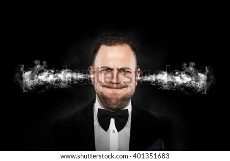 Stressful man with smoke or fume coming out from his ears on dark background. - stock photo