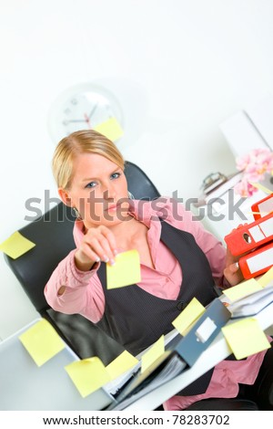 Stressful modern business woman sitting at workplace and stretches out hand with blank sticky notes - stock photo