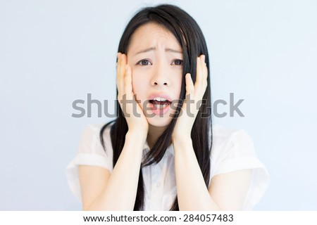 stressful young business woman against light blue background - stock photo