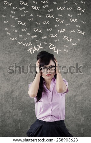Stressful young female entrepreneur counting her tax in front of gray background - stock photo