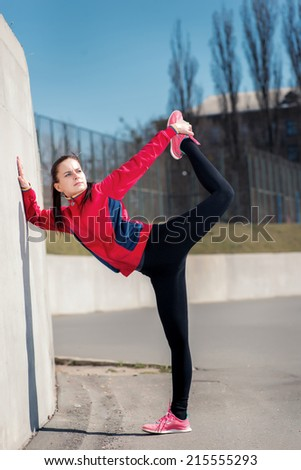 Stretching and twine! Young attractive girl in a sports clothing does warm up and stretching on the street the stadium in the afternoon. - stock photo