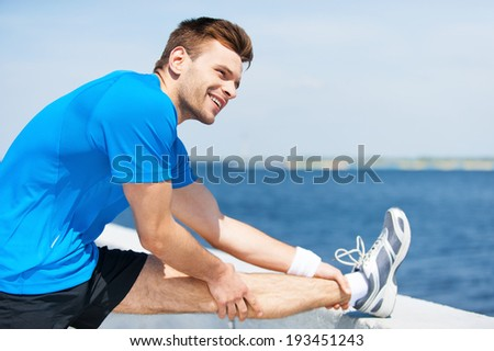 Stretching before running. Handsome young man doing stretching exercises and smiling while standing outdoors  - stock photo