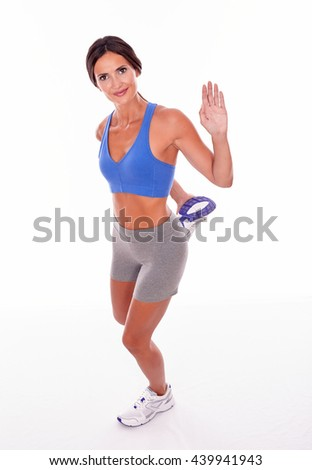 Stretching brunette woman holding a leg behind her and waving while looking at camera smiling and wearing blue and grey casual clothing, isolated - stock photo