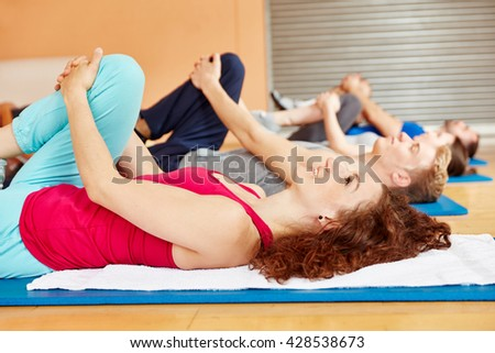 Stretching exercise during pilates class at fitness studio - stock photo