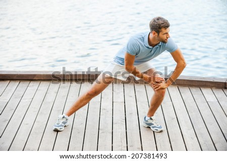 Stretching exercises. Confident young man doing stretching exercises while standing on quayside - stock photo