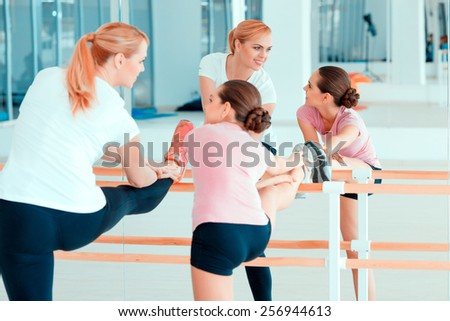 Stretching is a great start of the day. Beautiful mature woman and her teenage daughter in sports clothing warming up before the workout while standing against mirror in health club - stock photo